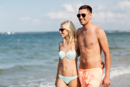 fling: love, travel, tourism, summer and people concept - smiling couple on vacation in swimwear and sunglasses holding hands and walking on beach