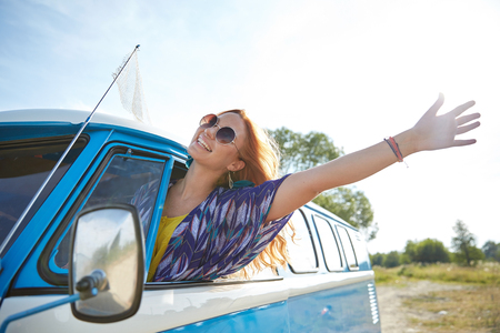 summer holidays, road trip, vacation, travel and people concept - smiling young hippie woman driving minivan car and waving hand Standard-Bild