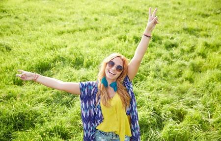 mujer hippie: naturaleza, verano, la cultura juvenil y la gente concepto - sonriente joven hippie mujer con gafas de sol bailando en el campo verde