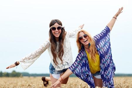 自然、夏、若者文化、友情、人コンセプト - 穀物のフィールド上で楽しんで若いヒッピー女性を笑顔