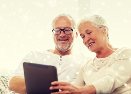 vecchiaia: famiglia, la tecnologia, l'età e le persone concetto - felice coppia senior con computer pc tablet di casa