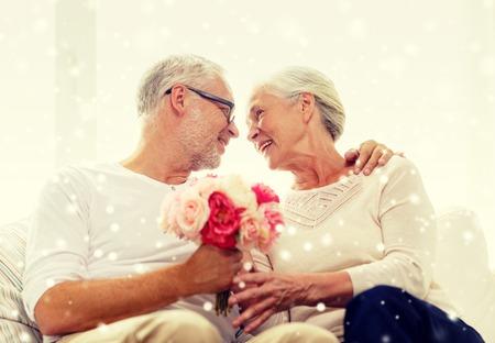 anniversaire: famille, vacances, l'âge et les gens notion - heureux couple senior avec bouquet de fleurs à la maison