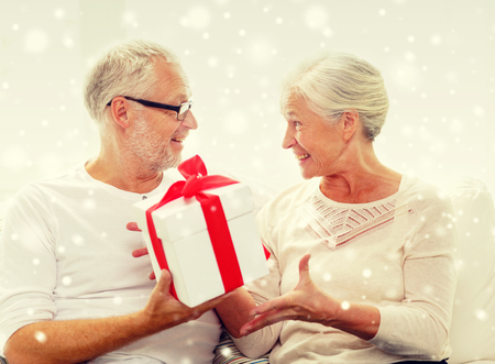 happy holidays: christmas ,family, holidays, age and people concept - happy senior couple with gift box and snow