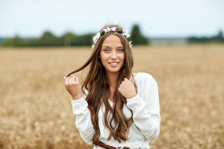 gipsy: nature, summer, youth culture and people concept - smiling young hippie woman wearing flower wreath on cereal field Stock Photo
