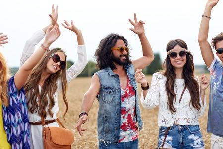 ragazze che ballano: natura, estate, cultura giovanile e persone Concetto - felice giovani amici hippy che ballano su campo di cereali