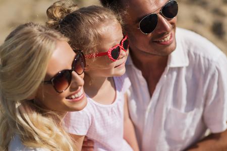 gafas de sol: familia, vacaciones, adopción y Concepto - hombre feliz, mujer y niña en gafas de sol en la playa de verano