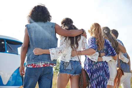 hippie: summer holidays, road trip, vacation, travel and people concept - young hippie friends hugging over minivan car from back