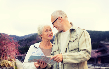 old asian: family, age, tourism, travel and people concept - senior couple with map and over asian village and mountains landscape background Stock Photo
