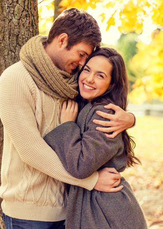 lovers park: love, relationship, family and people concept - smiling couple hugging in autumn park Stock Photo