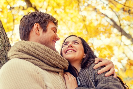 hispanic family: love, relationship, family and people concept - smiling couple hugging in autumn park Stock Photo