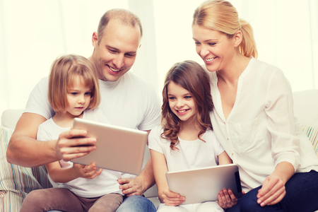 learning computer: family, children, technology, money and home concept - smiling family and two little girls with tablet pc computers at home