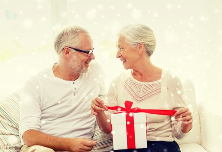 cute christmas: family, holidays, christmas, age and people concept - happy senior couple with gift box at home