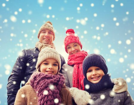 clothes winter: family, childhood, season and people concept - happy family in winter clothes over blue snowy background Foto de archivo
