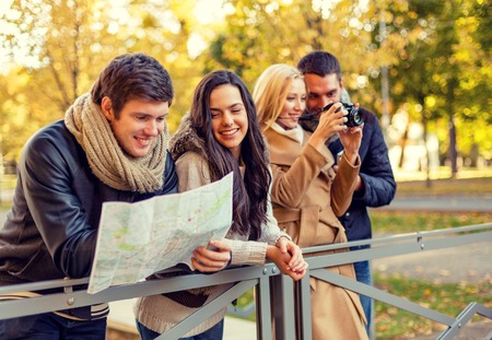 travel, vacation, technology, tourism and friendship concept - group of smiling friends with digital photo camera and map in city park