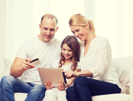 beautiful preteen girl: family, child, technology, money and home concept - smiling parents and little girl with tablet pc and credit card at home