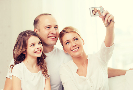 generation: family, child, photography and home concept - happy family with little girl making self portrait with digital camera