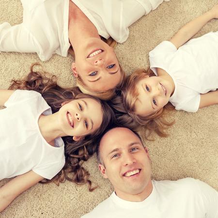 Famiglia, bambini e casa concetto - sorridente famiglia e due bambine che giace in cerchio sul pavimento a casa Archivio Fotografico - 47872207