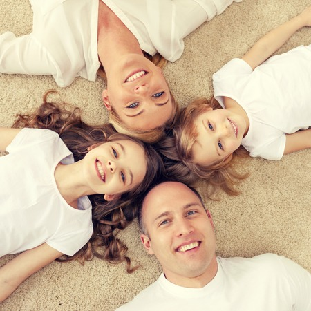 sonriente: familia, niños y concepto de hogar - familia sonriente con dos niñas pequeñas y se extiende en círculo en el suelo en el hogar Foto de archivo