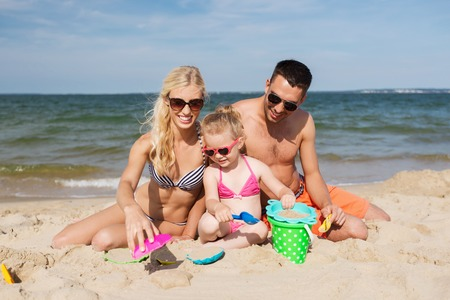 child couple: family, travel, vacation and people concept - happy man, woman and little girl in sunglasses playing with sand toys on summer beach
