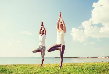 фитнес: фитнес, спорт, дружба и образ жизни концепция - улыбается пара, делая упражнения йоги на открытом воздухе Фото со стока