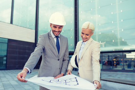 partnership: business, partnership, architecture and people concept - smiling businessman and businesswoman with blueprint and helmets on city street
