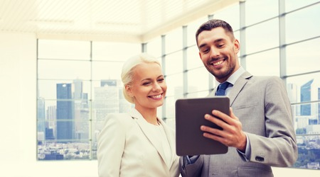 partnership: business, partnership, technology and people concept - smiling businessman and businesswoman with tablet pc computer over office room or new apartment background