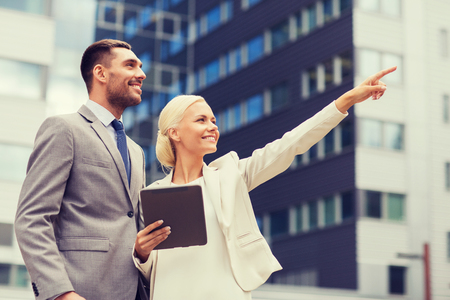 business partnership: business, partnership, technology and people concept - smiling businessman and businesswoman with tablet pc computer over office building Stock Photo