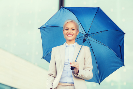 beautiful umbrella: business, bad weather and people and concept - young smiling businesswoman with umbrella outdoors
