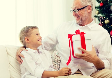 grandfather and grandson: family, holidays, generation, christmas and people concept - smiling grandfather and grandson with gift box sitting on couch at home