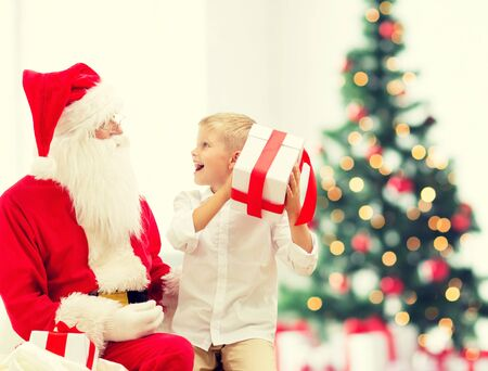 little boys: holidays, childhood and people concept - smiling little boy with santa claus and gifts over christmas tree lights background