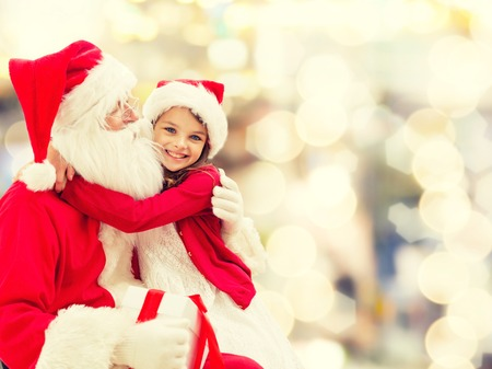 santa girl: holidays, christmas, childhood and people concept - smiling little girl hugging with santa claus over lights background