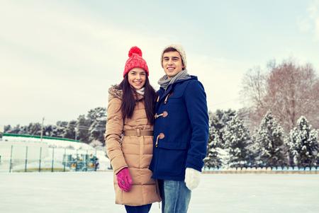 amistad: gente, invierno, la amistad, el amor y el concepto de ocio - feliz pareja de patinaje sobre hielo en pista al aire libre Foto de archivo