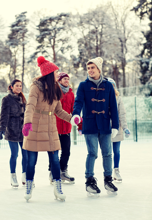 leisure activities: people, winter, friendship, sport and leisure concept - happy friends ice skating on rink outdoors Stock Photo