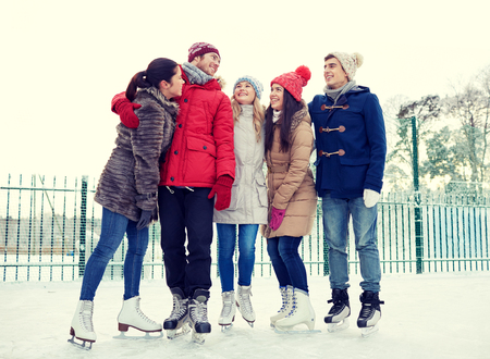 iceskates: people, winter, friendship, sport and leisure concept - happy friends ice skating and hugging on rink outdoors