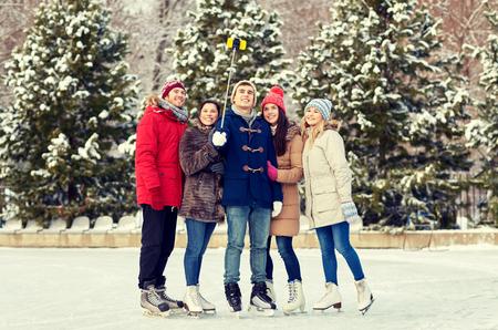 patinaje sobre hielo: la gente, la amistad, la tecnología y el concepto de ocio - amigos felices que toman el cuadro con el palillo Autofoto smartphone en pista de patinaje sobre hielo al aire libre