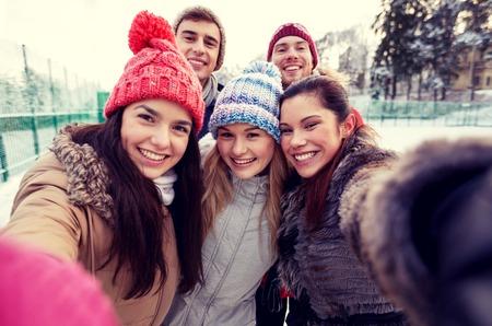 amistad: la gente, la amistad, la tecnología, el invierno y concepto de ocio - amigos felices que toman Autofoto con el teléfono inteligente o una cámara al aire libre