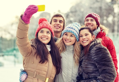 leisure: people, friendship, technology, winter and leisure concept - happy friends taking selfie with smartphone outdoors