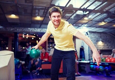 guys: people, leisure, sport and entertainment concept - happy young man throwing ball in bowling club