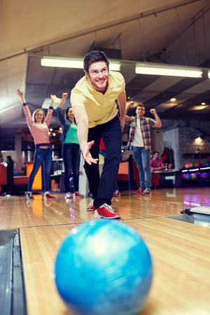 bolos: la gente, el ocio, el deporte y el concepto de entretenimiento - hombre joven y feliz de pelota en el club de bolos