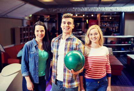 entertainment concept: people, leisure, sport, friendship and entertainment concept - happy friends in bowling club