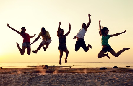 jumps: friendship, summer vacation, holidays, party and people concept - group of smiling friends dancing and jumping on beach Stock Photo