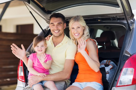 waving: transport, leisure, road trip and people concept - happy family with little girl sitting on trunk of hatchback car and waving hands at home parking space