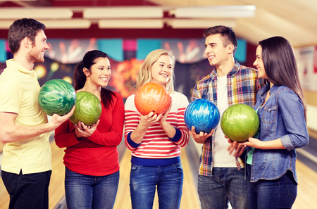 people, leisure, sport, friendship and entertainment concept - happy friends holding balls and talking in bowling club Imagens