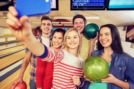 人、レジャー、スポーツ、友情、エンターテイメント コンセプト - ボウリング クラブでスマート フォンで selfie を取って幸せな友達