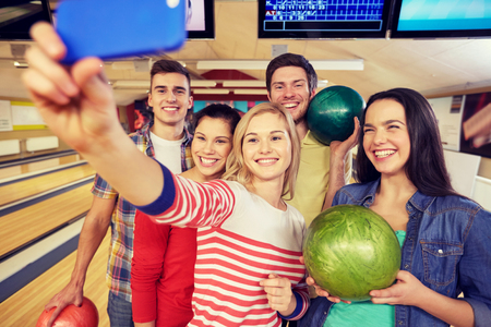 people, leisure, sport, friendship and entertainment concept - happy friends taking selfie with smartphone in bowling club 版權商用圖片