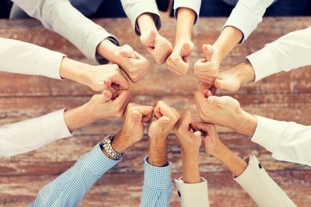 het bedrijfsleven, mensen, gebaar en teamwerk concept - close-up van het creatieve team duimen opdagen en zitten aan tafel in het kantoor