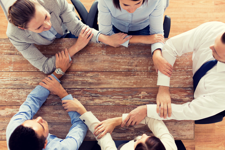 people office: business, people, cooperation and team work concept - close up of creative team sitting at table and holding hands in office