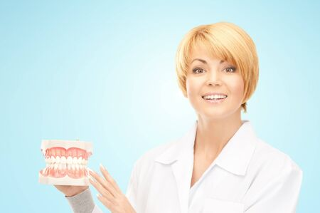 stomatology: medicine, stomatology, people and dental hygiene concept - smiling female doctor with jaws model over blue background