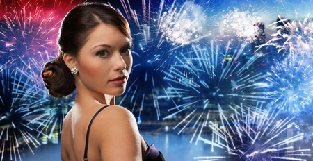 hollywood christmas: people, holidays and glamour concept - beautiful woman with diamond earring over nigh city and firework background