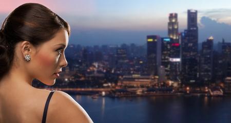 사람들, 휴일, 보석과 고급 개념 - 밤 싱가포르 도시 배경 위에 다이아몬드 귀걸이와 여자 얼굴